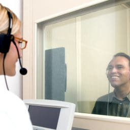 Man receiving a hearing test in a hearing booth looking through a glass window to a female audiologist